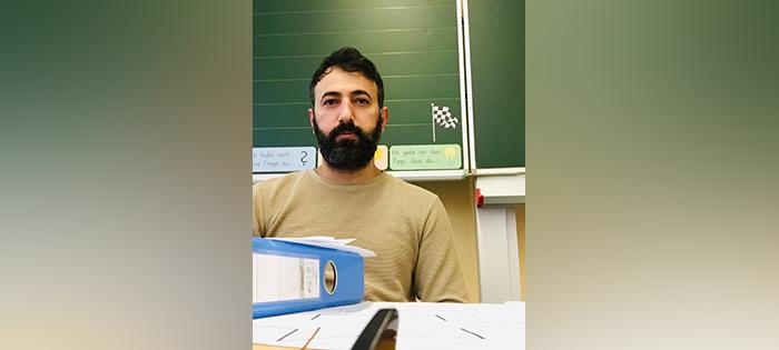 Ein Lehrer sitzt hinter seinem Schreibtisch.