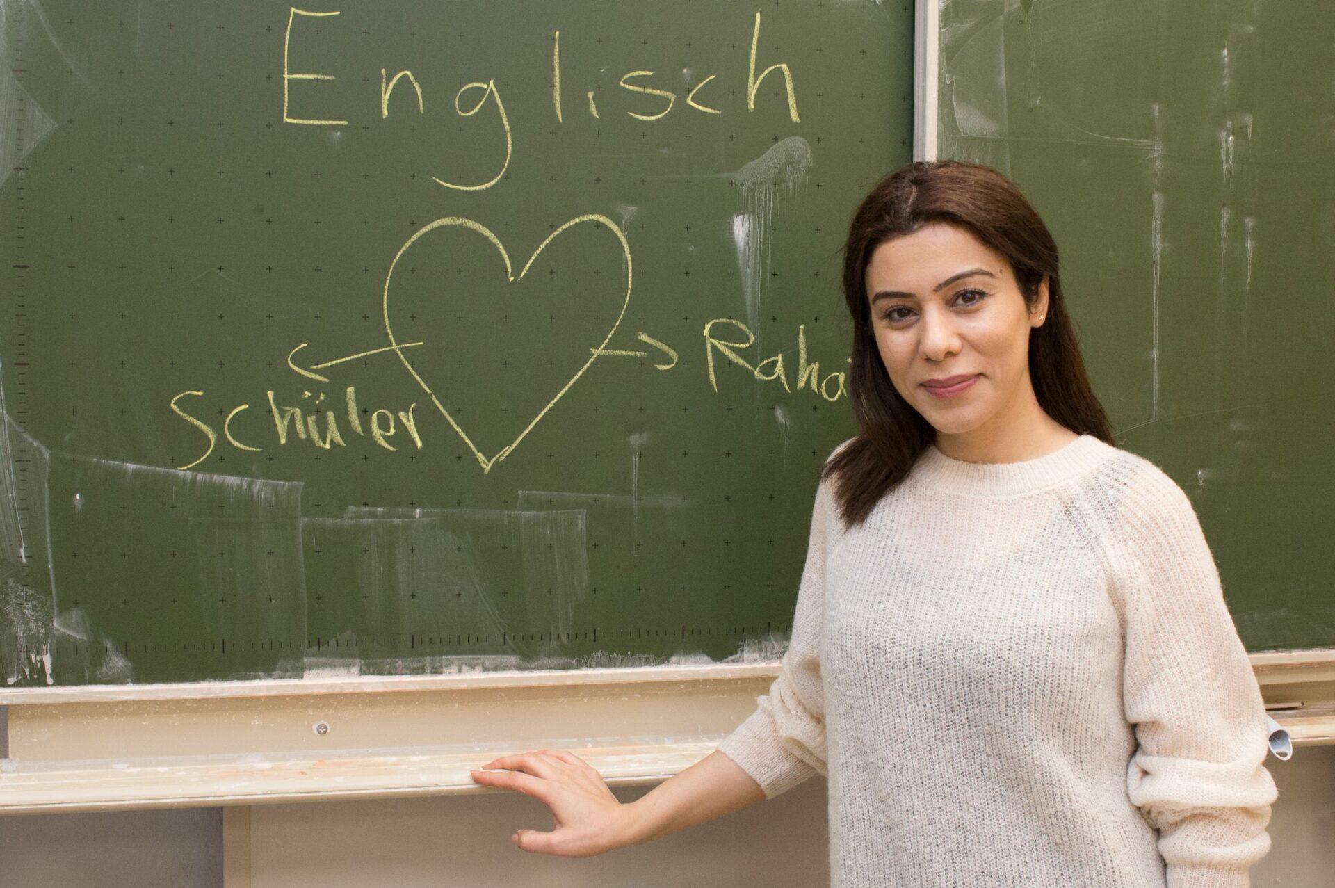 """Dunkelhaarige Lehrerin steht vor einer Tafel, auf die ein Herz gemalt wurde und das Wort """"Englisch"""" steht."""